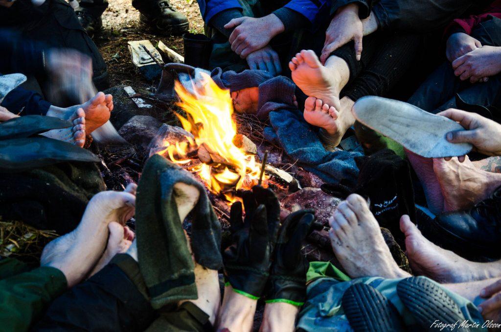 En grupp torkar våta fötter kring en värmande eld vid teambuilding i skogen