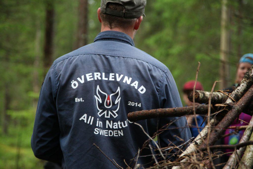 Ryggtalvan på en överlevnadsinstruktörmed trycket All in Nature SWEDEN.