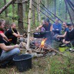 En teambuildinggrupp killar och tjejer lagar mat kring elden i sitt skydd i skogen ett event utöver det vanliga