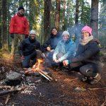 Skogen och elden skapar snabbt gemenskap Killar och tjejer sitter vid elden som de själva skapat