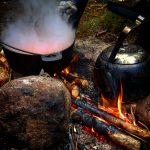 Mat lagas över över öppen eld i en gryta och kokkaffet står på elden