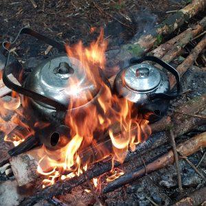 två kittlar med kokkaffe står på en rejäl eld och värms