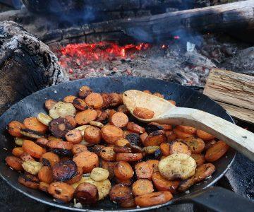 Stekpanna med grönsaker och korv över öppen eld