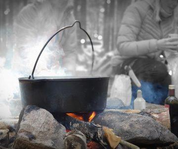 En fältgryta står på stenar över en fin liten eld