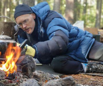 En man i blå jacka petar in ett vedträ i elden, på elden står en kaffekittel