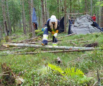 En tjej i gul jacka sågar ett träd med en vikbar såg