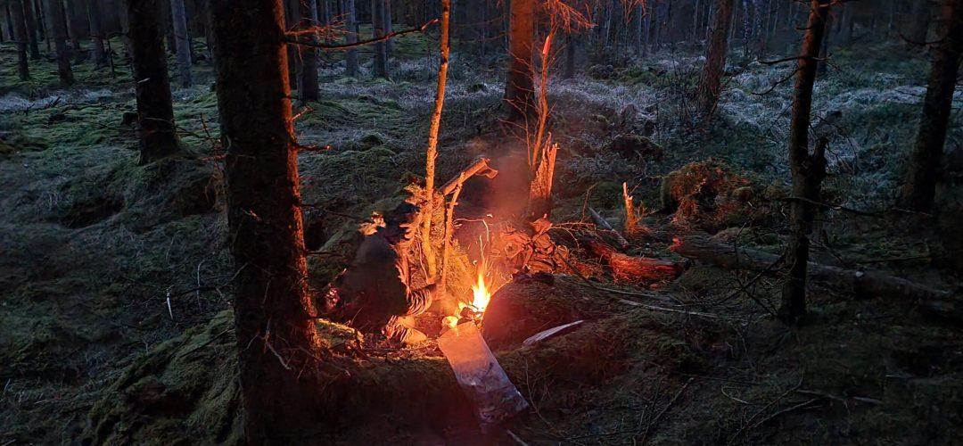 En person framför elden en mörk kväll.