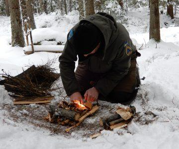 Torbjörn selin sitter på knä och tänder en liten eld i snön