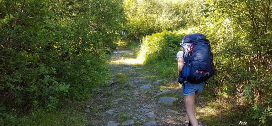 Kvinna övar vandringsteknik på en skogsled med tung ryggsäck