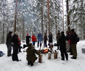 En grupp människor är samlade för genomgång under en eldkurs på vintern, en brasa i mitten