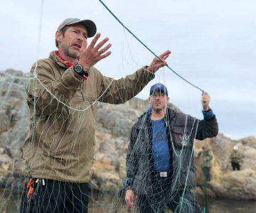 Instruktör visar upp ett handgjort fiskenät