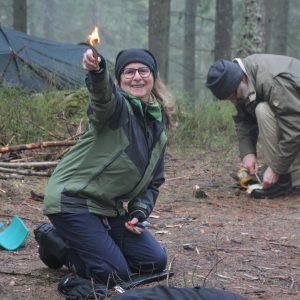 En kvinna som går en eldkurs har precis tänt näver med tändstål och håller upp brinnande näver i luften