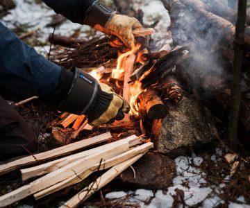 Torbjörn vårdar en lite större eld och lägger varsamt i pinnar snö på marken och handskar på händerna
