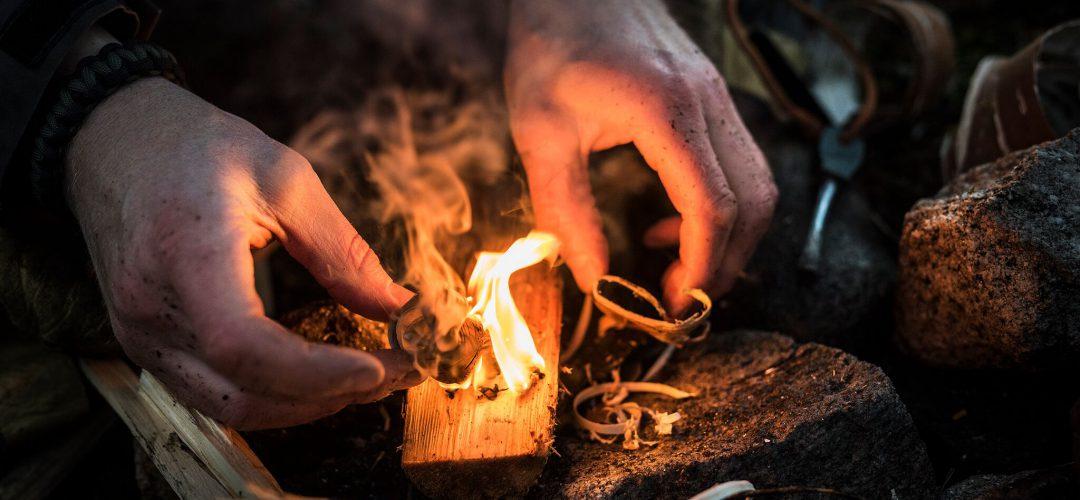 Två händer vid en liten eld av näver första steget vid tändning
